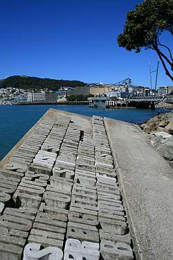 I had to scrabble over boulders to get this shot. Foreground is Denis Glover's plaque from the Wellington Writers' Walk; background, HMNZS Te Kaha at quayside, Te Papa national museum background (the Tracy Island look-alike).