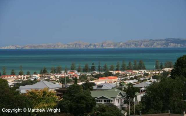 View of the town centre with Clifton and Cape Kidnappers across the bay beyond.