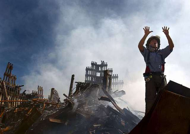 A fireman calls for 10 more colleagues amidst the ruins of the World Trade Centre, 10 September 2001. US Navy, Public Domain, via Wikimedia Commons.